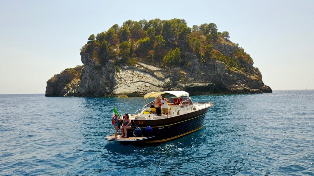 Modern gozzo boat with a rocky island on the sea