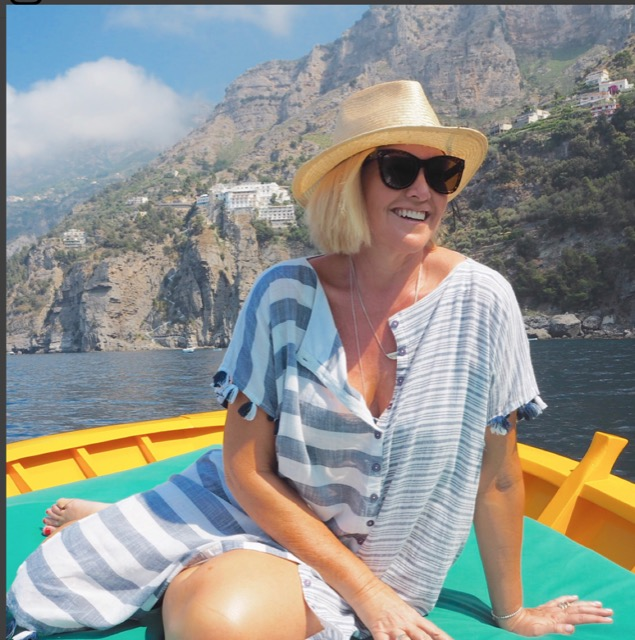 A blonde woman with hat and sunglasses on the boat