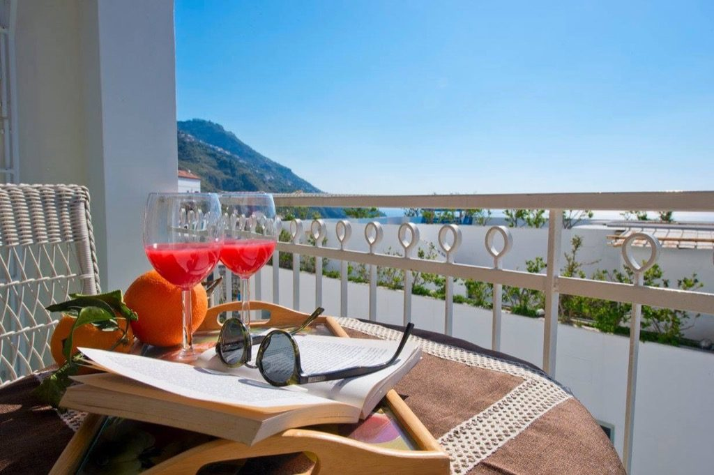 Casa Coccinella terrace with book sunglasses and drinks on the table