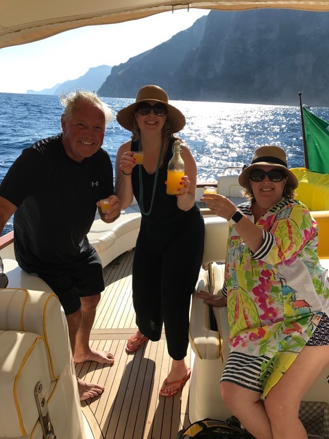 An happy family drinking limoncello on the boat