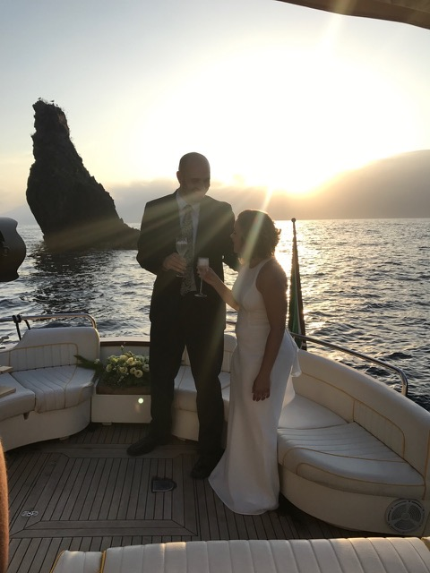 A married couple after wedding drinking prosecco on the boat