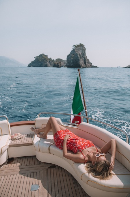 Model sunbathing on a modern gozzo boat in Amalfi Coast sea