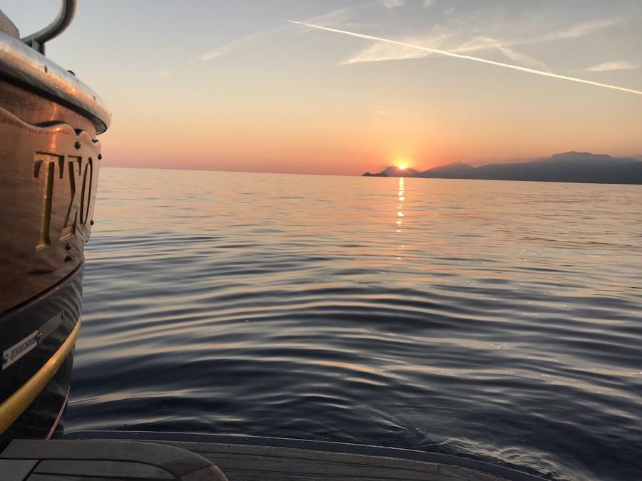 Il sole al tramonto sull'orizzonte della Costiera Amalfitana visto dalla barca