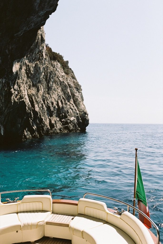 Back of a gozzo boat with crystal sea water and rock cave