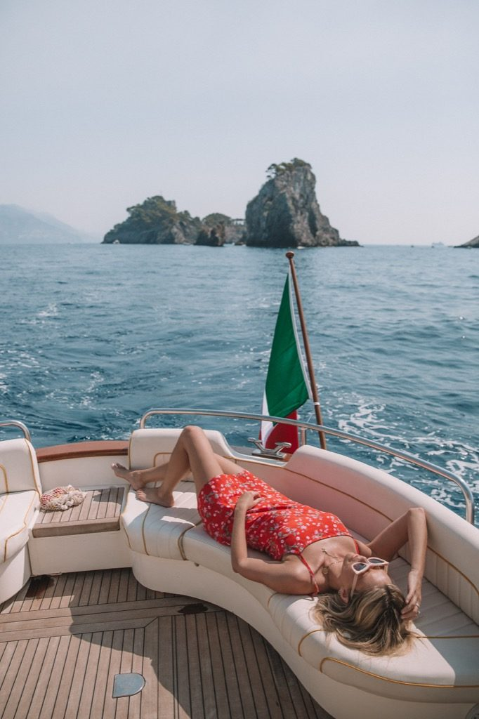A model sunbathing on the back of a gozzo boat with sea and an island