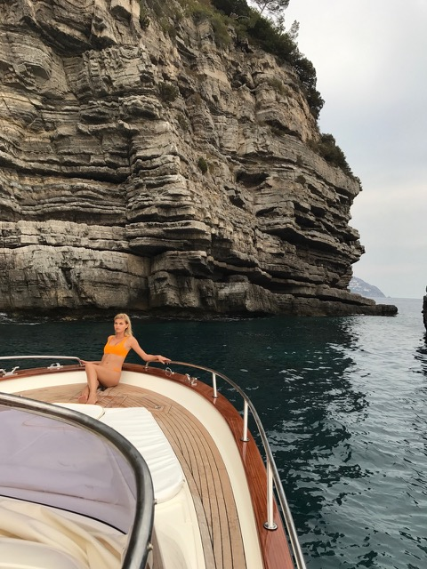 A blonde girl sunbathing on the front of the gozzo boat