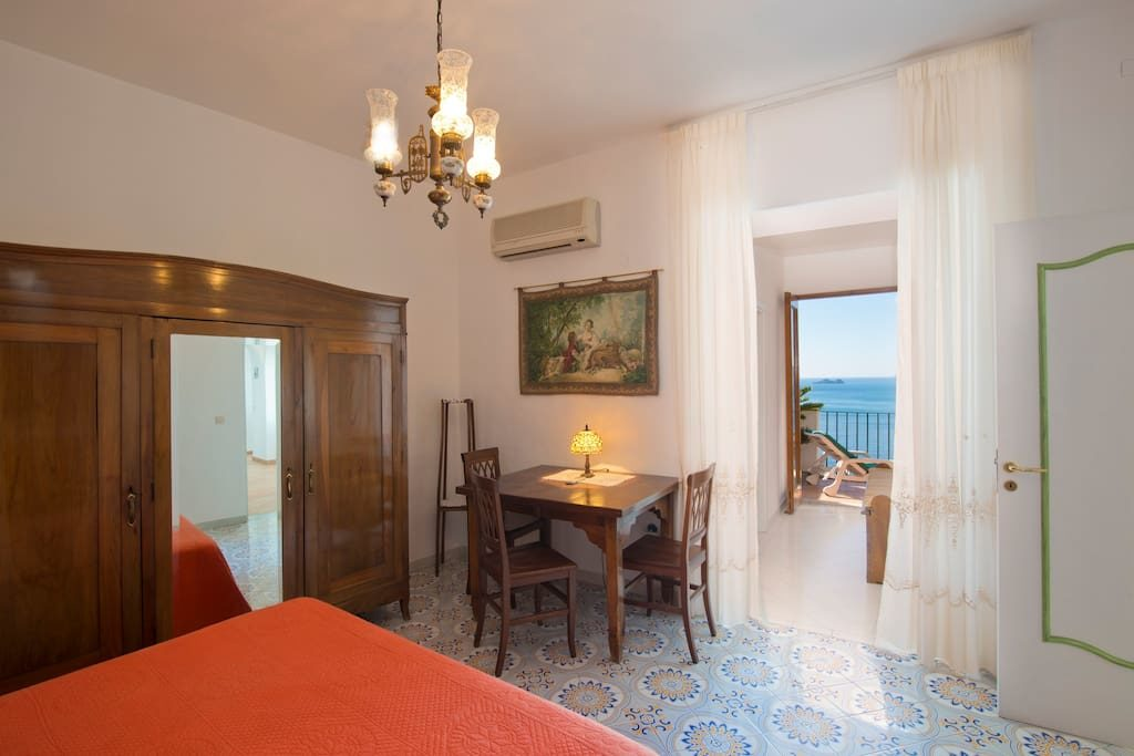 Casa Regina interior bedroom with table and terrace on the sea