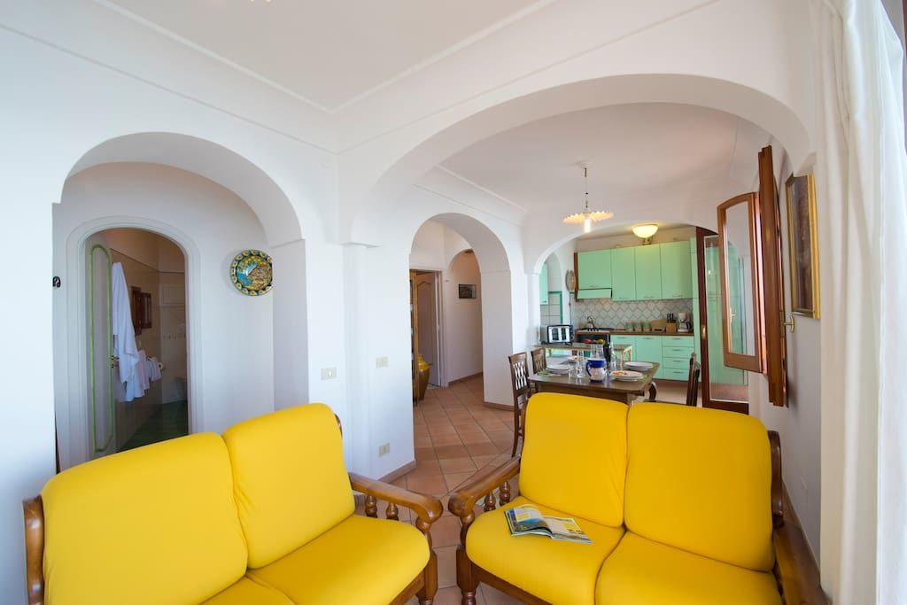 Casa Regina interior living room with yellow sofas