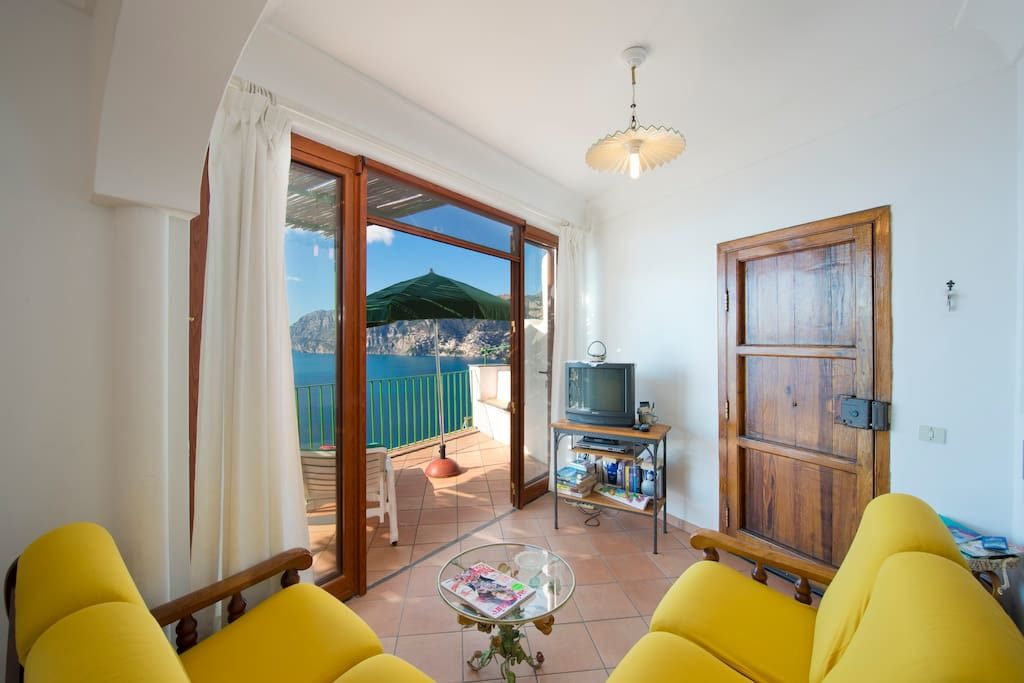Casa Regin interior living room with yellow sofa and terrace on the sea