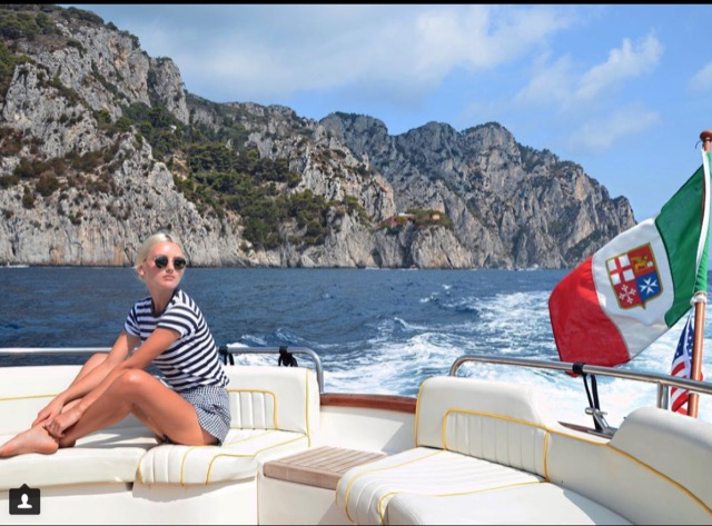 A girl sitting on the back of the boat with sea waves and the Coast