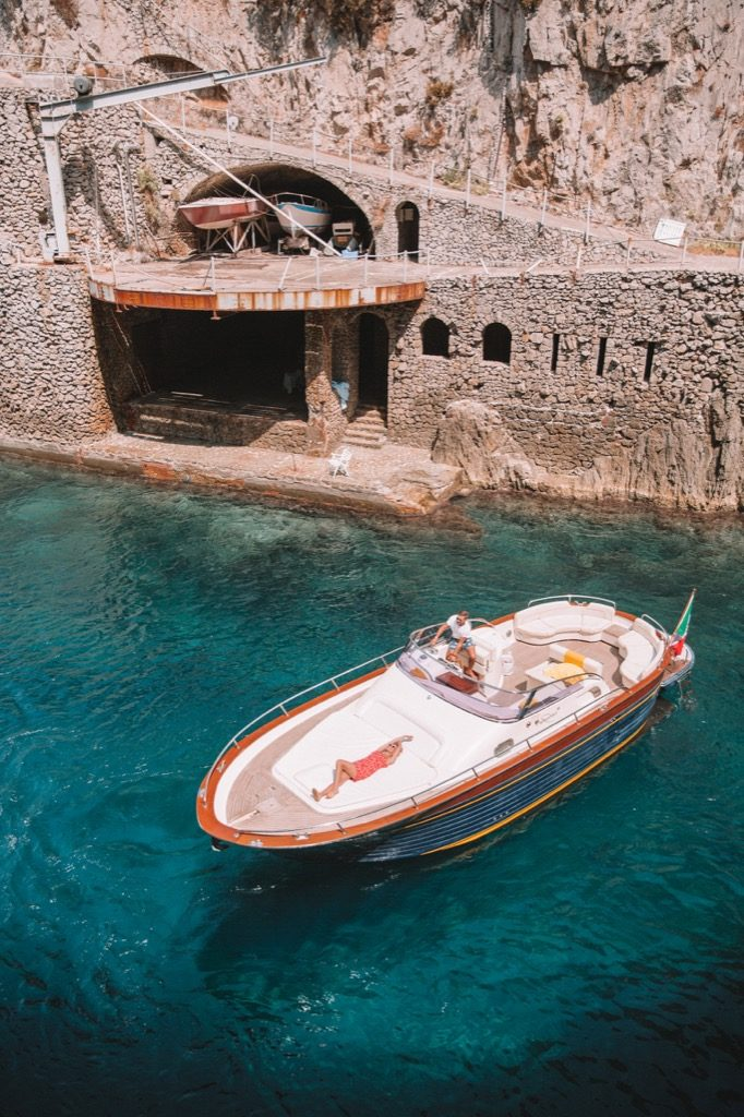 Gozzo boat view from above with crystal water of the sea and a model sunbathing