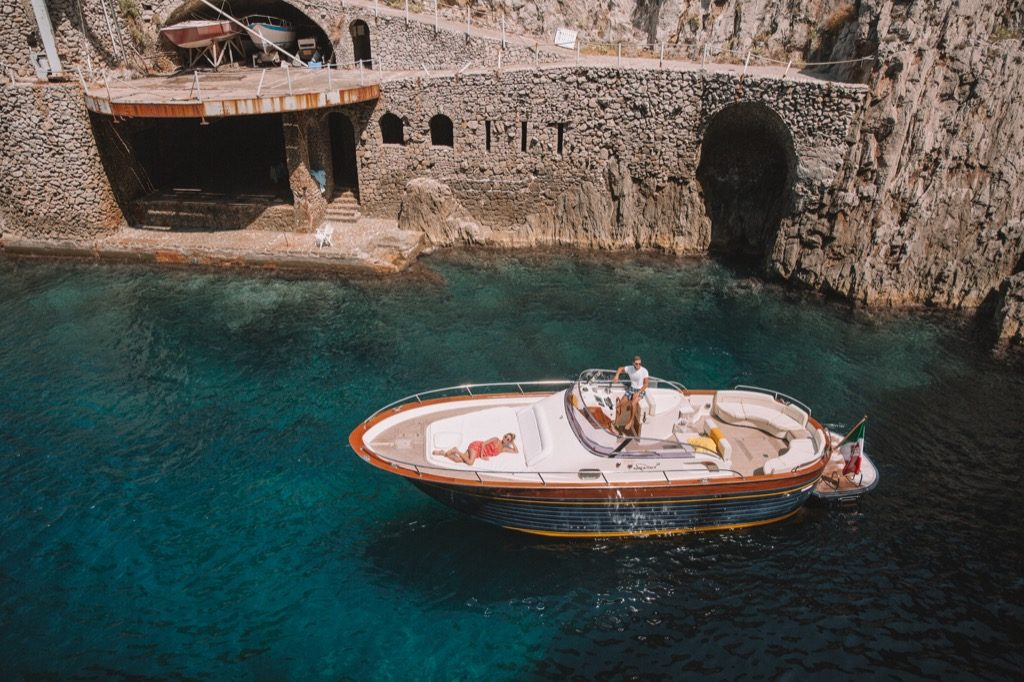 Gozzo boat view from above with a model sunbathing over sea water