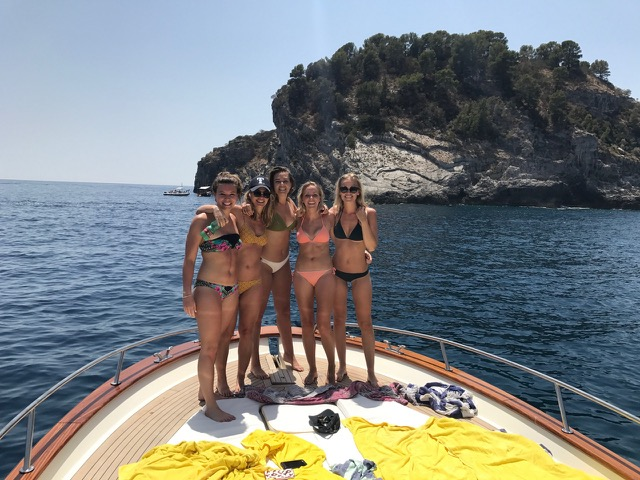 A group of girls standing on the front of the boat with an island on the sea