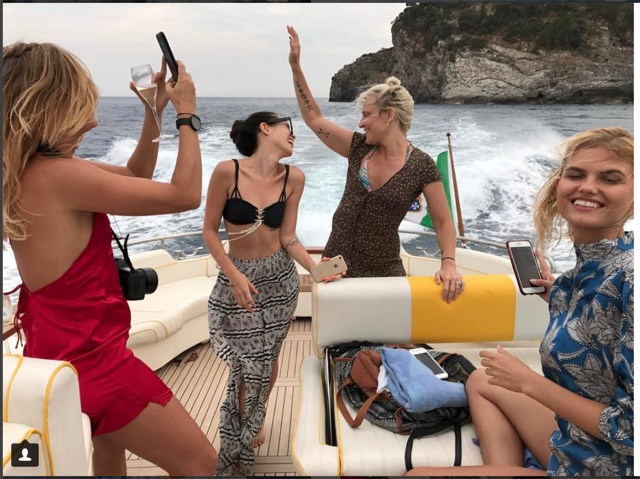 Happy girls joking on the boat with sea waves