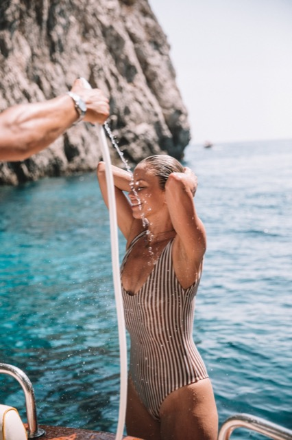 A model taking a shower with fresh sea water in the back of the boat