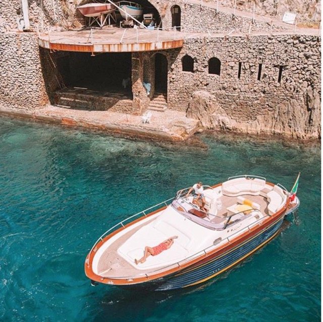 Modern gozzo boat with a model sunbathing