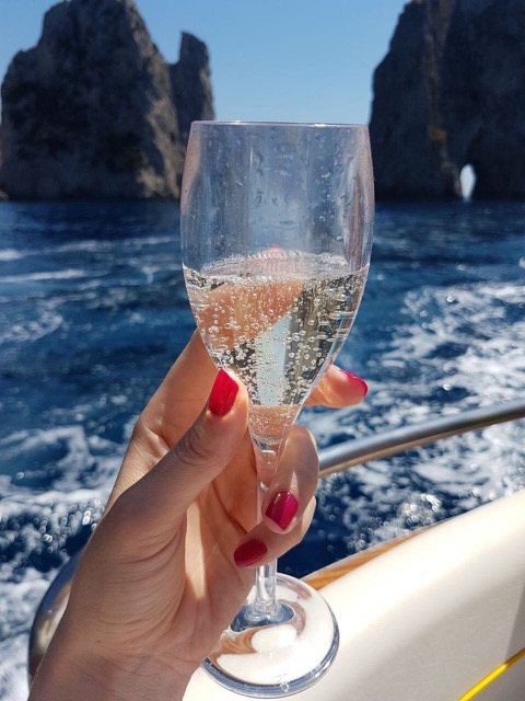 Prosecco glass in the hand with red nails on the boat in the sea
