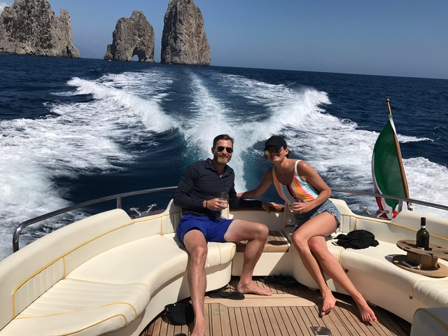 A young couple on the back of the boat with waves