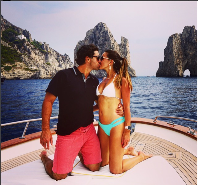 A young couple kissing on their knees on the boat with sea and rocks